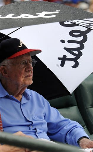 Former President Jimmy Carter watches the New York Yankees against the Atlanta Braves baseball game from under an umbrella on Wednesday, June 13, 2012, in Atlanta. (AP Photo/John Amis)