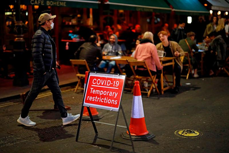 People drink at the outside tables in central London (AFP via Getty Images)