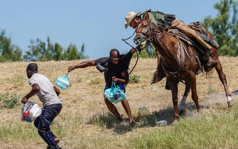A United States Border Patrol agent on horseback tries to stop a Haitian migrant from entering an encampment on the banks of the Rio Grande - PAUL RATJE/AFP via Getty Images