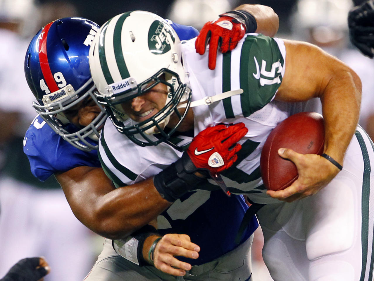 New York Giants linebacker Spencer Paysinger (49) tackles New York Jets quarterback Tim Tebow (15) during the second half of a preseason NFL football game on Saturday, Aug. 18, 2012, in East Rutherford, N.J. (AP Photo/Rich Schultz)