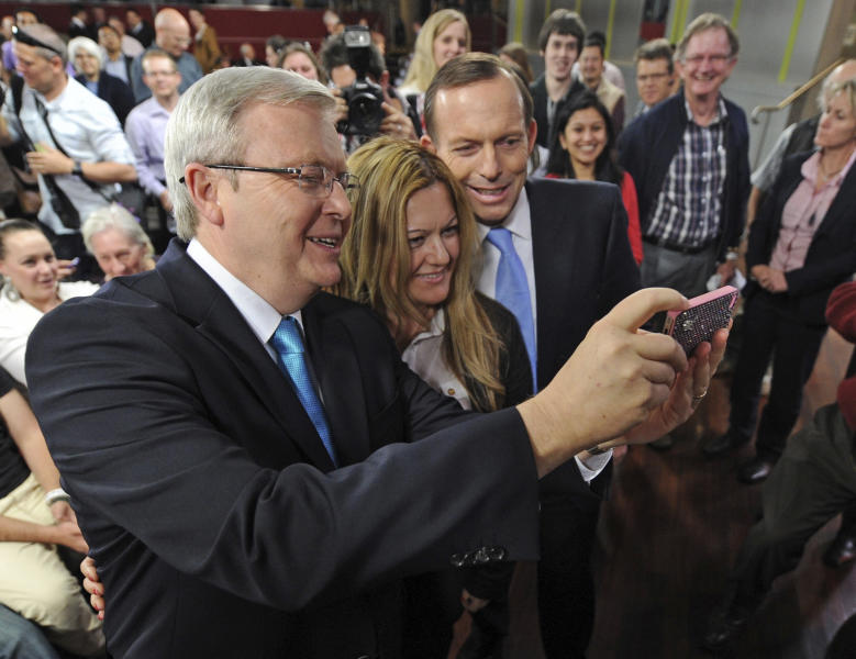 """FILE - In this Wednesday, Aug. 28, 2013 file photo, Australian opposition leader Tony Abbott, third from left, and Prime Minister Kevin Rudd, left, pose for a photo with audience member Nada Makdessi following a public forum in Sydney. Abbott, the political pugilist who leads Australia's opposition, was once dubbed """"unelectable"""" by a former boss, but as Sept. 7, 2013 elections near he seems certain to become prime minister. Abbott's conservative coalition now holds a commanding lead in opinion polls, though the man himself surpassed Rudd in popularity only this week in a poll by Sydney-based market researcher Newspoll. In July, Rudd had been the clear favorite, 50 percent to 34 percent. (AP Photo/Lukas Coch, Pool, File)"""