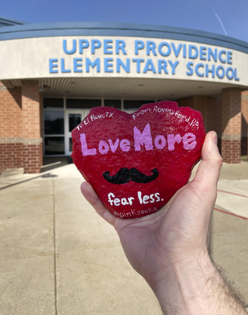 """In this March 2021 photo provided by teacher Brian Aikens, Aikens holds up a heart-shaped """"kindness rock"""" memorializing Texas teacher Zelene Blancas, who died of COVID-19 in December 2020, outside Upper Province Elementary School in Royersford, Pa. The stone was decorated and transported across the country by a handful of people to El Paso's Dr. Sue A. Shook Elementary School, where Blancas taught and was remembered by her principal as someone who """"embodied kindness."""" (Brian Aikens via AP)"""