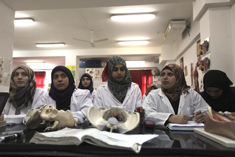 In this Wednesday, April 9, 2014 photo, Palestinian students attend a lesson in the Faculty of Medicine at the Al-Quds University in the West Bank village of Abu Dis, near Jerusalem. Dozens of Palestinian doctors who graduated from Al-Quds University, a school that has a foothold in east Jerusalem, are caught in the political battle between Israel and the Palestinians over the city's eastern sector. Israel has refused to recognize the university's graduates -- a move that could amount to acknowledging the Palestinian claims to east Jerusalem as their capital. (AP Photo/Majdi Mohammed)