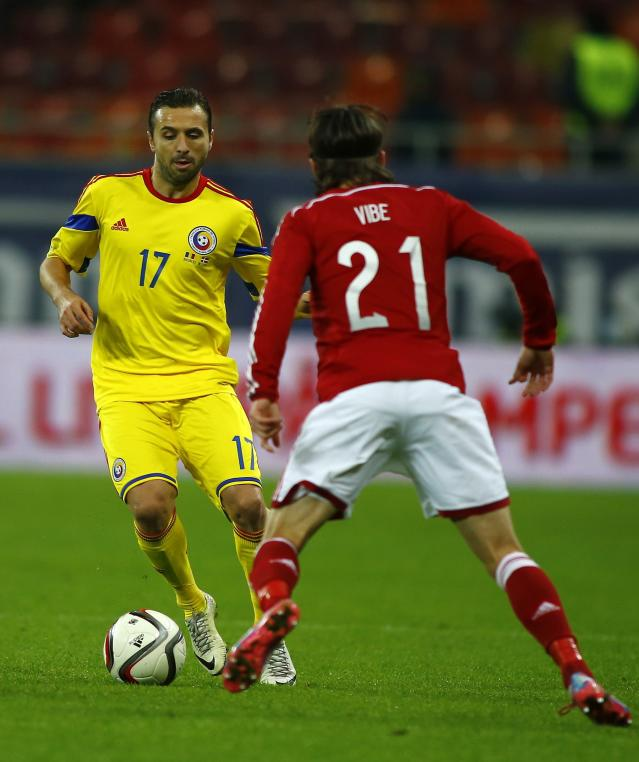 Romania's Lucian Sanmartean (L) is challenged by Denmark's Lasse Vibe during their international friendly soccer match at National Arena in Bucharest November 18, 2014. Romania have reaped the rewards of a rejuvenated Sanmartean after the veteran returned following a three-year break to become instrumental in guiding the team to the top of their Euro 2016 qualifying group. The 34-year-old midfielder was named in Romania's starting lineup for the eagerly-anticipated clash with neighbours Hungary last month, his first international appearance since playing 28 minutes of a Euro 2012 qualifier against Belarus on October 7, 2011. REUTERS/Bogdan Cristel (ROMANIA - Tags: SPORT SOCCER)
