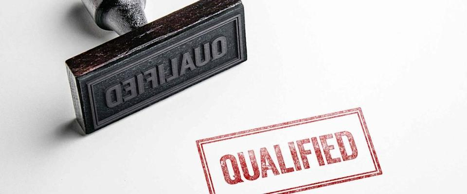 Rubber stamping that says 'Qualified'.