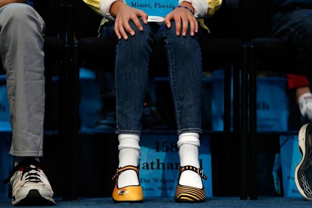 <p>Simone Kaplan, 11, of Davie, Fla., wears bee-themed shoes while competing in the 90th Scripps National Spelling Bee in Oxon Hill, Md., Wednesday, May 31, 2017. The first national spelling bee was held in 1925, and the contest was put on hold during World War II. (AP Photo/Jacquelyn Martin) </p>