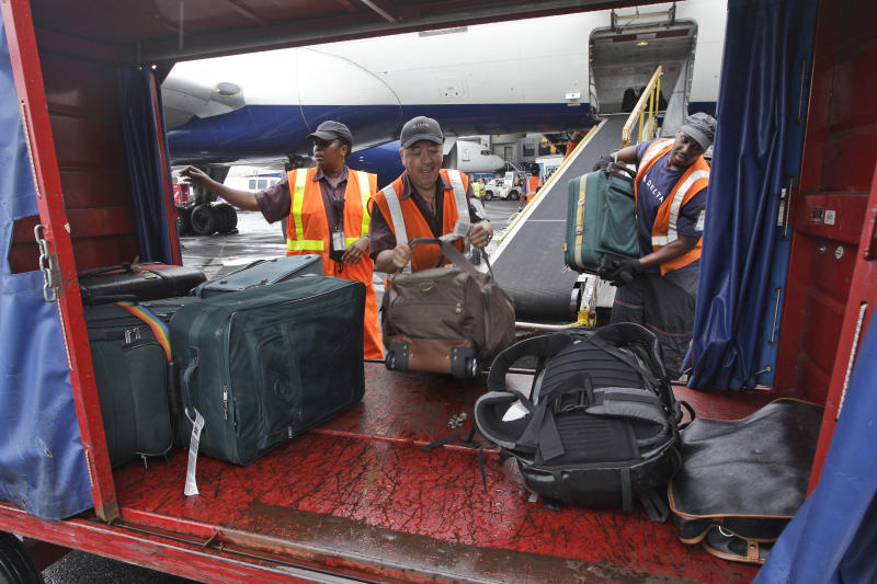 In this Wednesday, Aug. 1 2012 photo, Delta Air Lines ramp agents unload bags from a flight arriving at JFK International airport in New York. Travelers still have to put up with packed planes, rising fees and unpredictable security lines, but they are missing fewer business meetings or chances to tuck their kids into bed. Nearly 84 percent of domestic flights arrived within 15 minutes of their schedule time in the first half of the year, the best performance since the government started tracking such data in 1988. (AP Photo/Mary Altaffer)