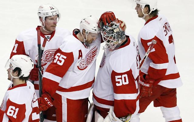 Detroit Red Wings players, including Daniel Alfredsson (11), Niklas Kronwall (55), Brendan Smith (2) and Xavier Ouellet (61) gather around goalie Jonas Gustavsson (50) after losing 4-2 to the Boston Bruins in Game 5 in the first round of the NHL hockey Stanley Cup playoffs in Boston, Saturday, April 26, 2014. The loss eliminated the Red Wings from the playoffs. (AP Photo/Michael Dwyer)