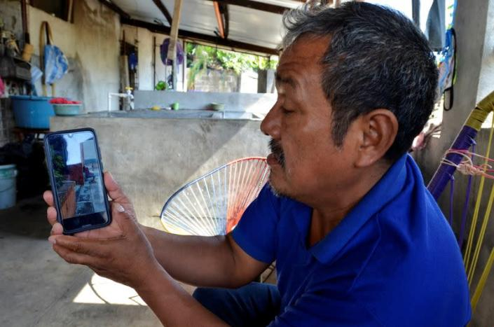 Gerardo Zacarias, who fears his daughter Paola Damaris is among the 19 bodies found shot and burnt in a remote part of northern Mexico, watches the news on his cell phone, in Catarina