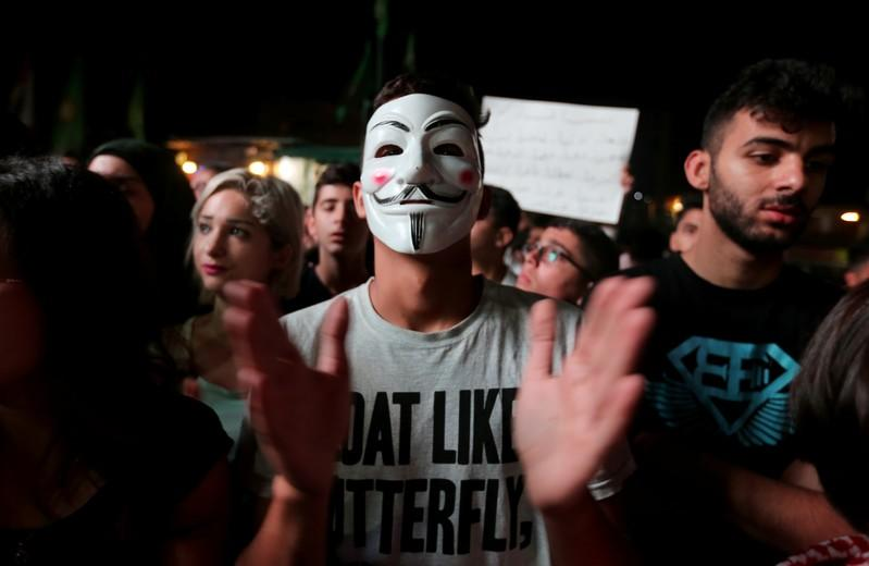 A demonstrator wears a mask during an anti-government protest in the southern city of Nabatiyeh
