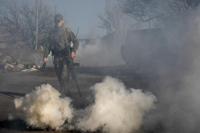 A Ukrainian serviceman makes smokescreen against military drones at a position near the front line as the conflict continues, in Mariinka, Donetsk region, eastern Ukraine, Saturday, April 20, 2019. The two presidential candidates standing for election on Sunday are pressing separate solutions for a resolution of the conflict in eastern Ukraine, where fighting with Russia-backed separatist rebels has killed more than 13,000 people since 2014. (AP Photo/Evgeniy Maloletka)