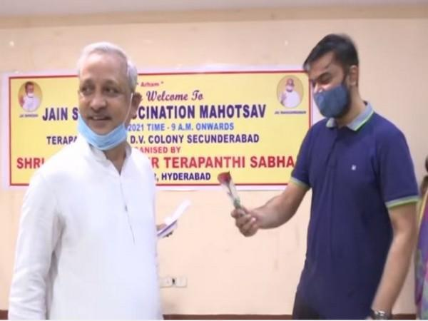 Member of Jain community offering rose to a beneficiary of vaccination drive (Photo/ANI)