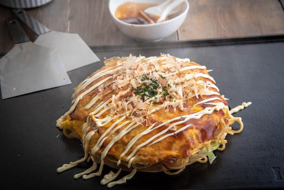 In Japan, the pancake is a savory entree, topped with meats, seafood, veggies and cheese.