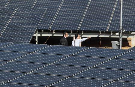 Japanese visitors walk through solar panels donated by Japan's government at a solar plant in Diriamba