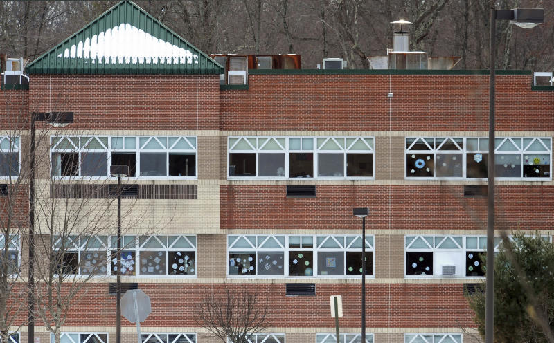 FILE - In this Jan. 2, 2013 file photo, snowflake artwork adorn windows at the new Sandy Hook Elementary School, on the day before the first day of classes in Monroe, Conn. Three months after the Newtown massacre, children and teachers who survived remain on edge. Signs in the new school ask people to close doors softly and not to drag objects across the floor during school hours, in an effort to help keep students and faculty at the school as calm as possible.  (AP Photo/Jessica Hill, File)