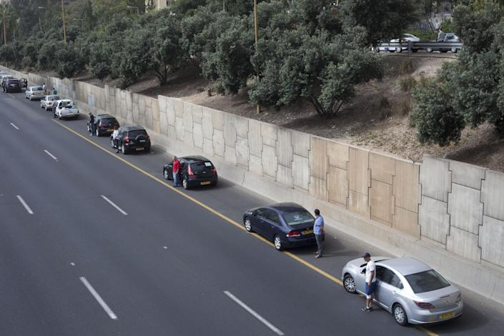Israeli motorists stand still next to their cars on a freeway as a two-minute siren sounds in memory of victims of the Holocaust in Tel Aviv, Israel, Monday, April 8, 2013. Holocaust remembrance day is one of the most solemn on Israel's calendar with restaurants and places of entertainment shut down, and radio and TV programming focused on Holocaust documentaries and interviews with survivors. (AP Photo/Ariel Schalit)