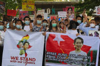 Migrant workers from Myanmar flash the three-finger protest gesture while they hold banners with images of deposed Myanmar leader Aung San Suu Kyi before participating in a march by Thai pro-democracy activists to the residence of Thai Prime Minister Prayuth Chan-ocha Sunday, Feb. 28, 2021 in Bangkok, Thailand. The group joined the march after Prayuth met with the Myanmar Foreign Minister Wunna Maung Lwin in Bangkok earlier in the week. Security forces in Myanmar have made mass arrests and appeared to use lethal force as they intensify their efforts to break up protests a month after the military staged a coup. (AP Photo/Fu Ting)