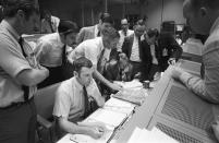 In this April 15, 1970 photo made available by NASA, a group of flight controllers gather around the console of Glenn S. Lunney, foreground seated, Shift 4 flight director, in the Mission Operations Control Room (MOCR) of Mission Control Center (MCC) in Houston. Their attention is drawn to a weather map of the proposed landing site in the Pacific Ocean. At this point, the Apollo 13 lunar landing mission had been canceled, and the problem-plagued Apollo 13 crew members were in trans-Earth trajectory attempting to bring their crippled spacecraft back home. (NASA via AP)