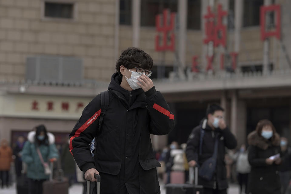 A man adjusts his face mask to help curb the spread of the coronavirus walks out from the Beijing railway station as passenger arrive in Beijing, Tuesday, Jan. 19, 2021. China is now dealing with coronavirus outbreaks across its frigid northeast, prompting additional lockdowns and travel bans. (AP Photo/Andy Wong)