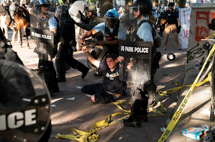 Riot police detain a man as they rush protesters to clear Lafayette Park on June 1. (Ken Cedeno/Reuters)
