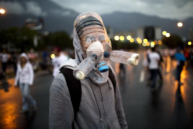 <p>A protester wearing a gas mask made from plastic water bottles poses for a picture during an opposition protest blocking a highway outside La Carlota airport in Caracas, Venezuela, Feb. 18, 2014.(Photo: Rodrigo Abd/AP) </p>