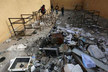 Students stand amid damaged desks and books in 'Aisha Mother of the BelieversÕ school which was recently reopened after rebels took control of al-Rai town from Islamic State militants, Syria January 17, 2017. Picture taken January 17, 2017. To match story MIDEAST-CRISIS/SYRIA-SCHOOL.   REUTERS/Khalil Ashawi