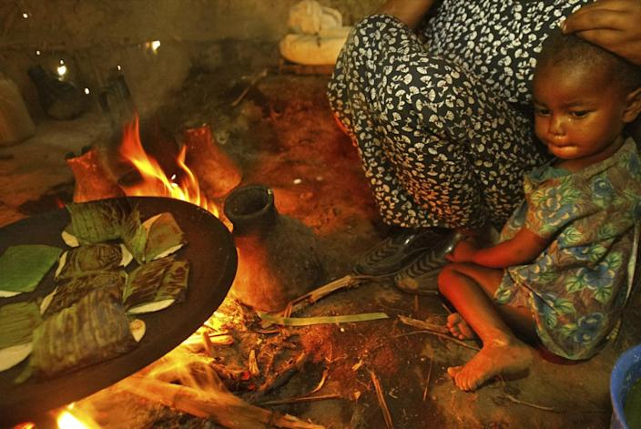 An infant sits with an adult near a cooking fire