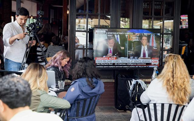 <p>People watch Former FBI Director James Comey testimony before the Senate Intelligence Committee on Capitol Hill at Shaw's Bar in Washington, D.C., June 8, 2017. (Tasos Katopodis/EPA) </p>