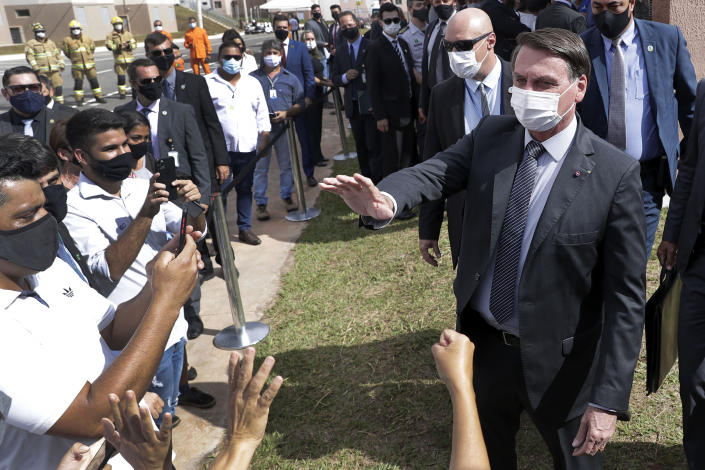 Wearing a mask to curb the spread of the new coronavirus, Brazil's President Jair Bolsonaro greets people after a ceremony to deliver affordable homes built by the government, in a neighborhood of Brasilia, Brazil, Monday, Apr. 5, 2021. (AP Photo/Eraldo Peres)