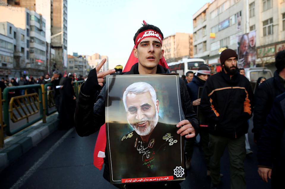 An Iranian man holds a picture of Qassem Soleimani during a funeral procession for Iranian Major-General Qassem Soleimani, head of the elite Quds Force, and Iraqi militia commander Abu Mahdi al-Muhandis, who were killed in an air strike at Baghdad airport, in Tehran, Iran January 6, 2020. Nazanin Tabatabaee/WANA (West Asia News Agency) via REUTERS ATTENTION EDITORS - THIS IMAGE HAS BEEN SUPPLIED BY A THIRD PARTY