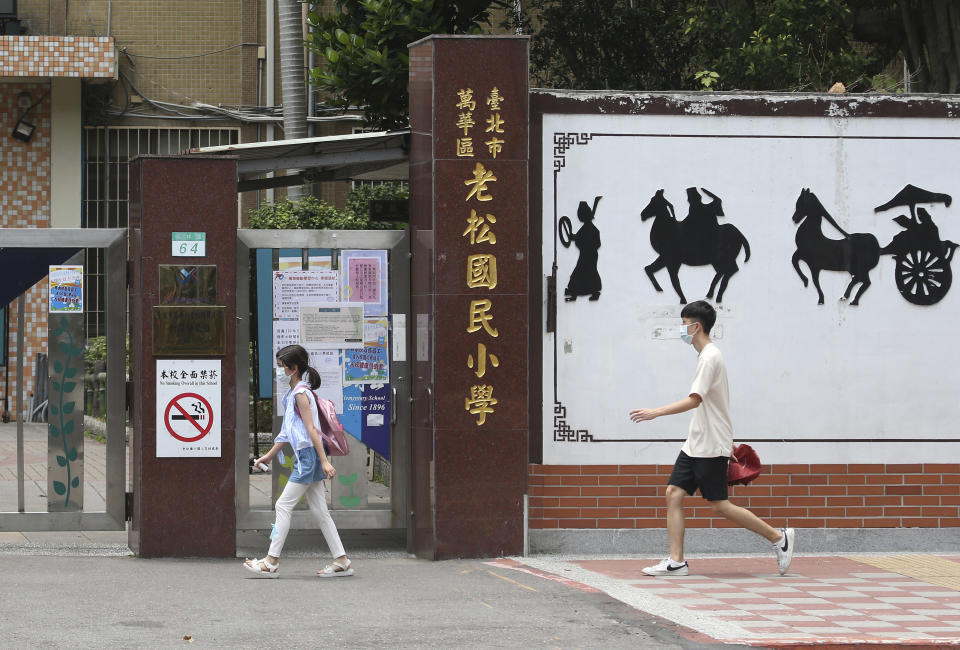 Students wearing face masks to protect against the spread of the coronavirus walk past a closed primary school after the COVID-19 alert raise to level 3 in Taipei, Taiwan, Tuesday, May 18, 2021. (AP Photo/Chiang Ying-ying)