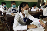 Students sit in their class room at Santhormok high school, in Phnom Penh, Cambodia, Monday, Nov. 2, 2020. Schools throughout Cambodia that had been shut in March because of the coronavirus crisis reopened Monday, but with limits on class sizes and hours.(AP Photo/Heng Sinith)