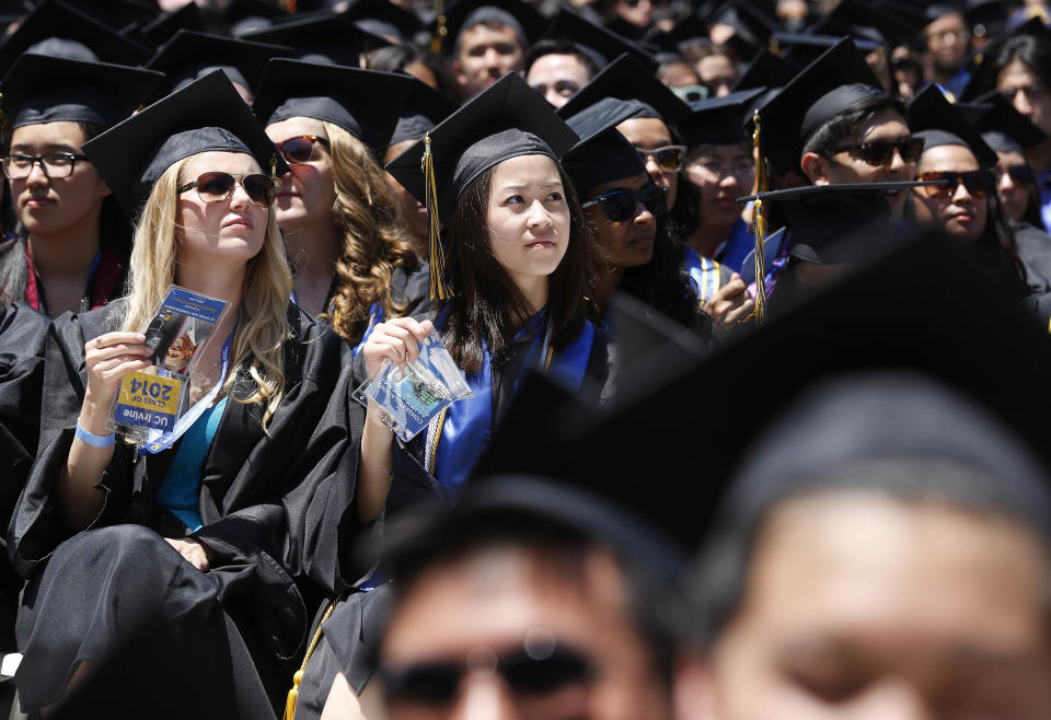 Graduates listen to U.S. President Barack Obama (not pictured) talk during the commencement ceremony for the University of California, Irvine at Angels Stadium in Anaheim, California June 14, 2014. REUTERS/Larry Downing (UNITED STATES - Tags: POLITICS EDUCATION)