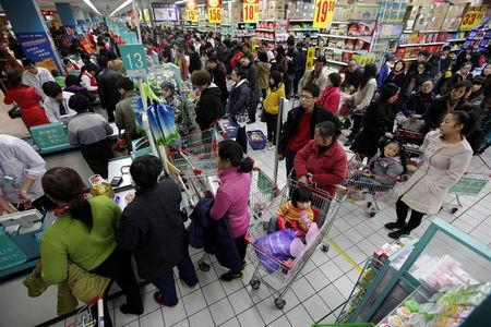 FILE PHOTO: Customers queue to pay as they shop at a Carrefour supermarket in Wuhan