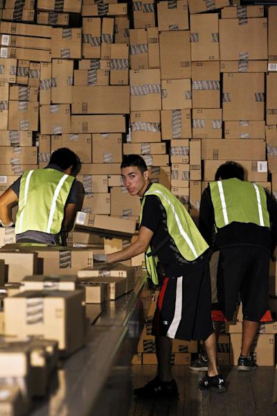 "Workers pack a shipping truck on ""Cyber Monday"" at the Amazon.com 1.2 million square foot fulfillment center Monday, Nov. 26, 2012, in Phoenix. Americans clicked away on their computers and smartphones for deals on Cyber Monday, which is expected to be the biggest online shopping day in history. Shoppers are expected to spend $1.5 billion on Cyber Monday, up 20 percent from last year, according to research firm comScore. That would not only make it the biggest online shopping day of the year, but the biggest since comScore started tracking shoppers' online buying habits in 2001. (AP Photo/Ross D. Franklin)"