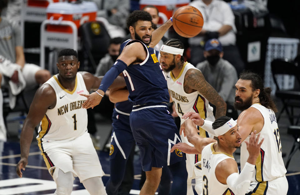 Denver Nuggets guard Jamal Murray, center, fires a pass while navigating through, from left, New Orleans Pelicans forwards Zion Williamson and Brandon Ingram, center Steven Adams and guard Josh Hart in the second half of an NBA basketball game Sunday, March 21, 2021, in Denver. The Pelicans won 113-108. (AP Photo/David Zalubowski)
