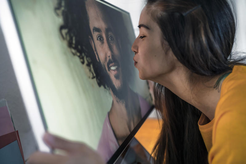 Young woman kissing man on computer screen