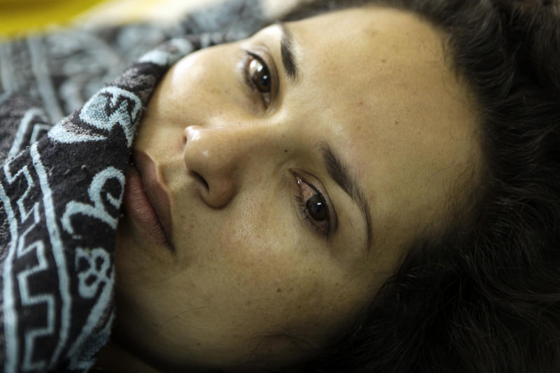 """In this Nov. 15, 2012 photo, Lucia Aguero lies in the hospital on the 50th day of her hunger strike in Coronel Oviedo, Paraguay. Aguero, a 25-year-old mother of two small children, was jailed after a chaotic pass through a hospital emergency room where doctors were too busy with the wounded to remove the bullet from her thigh. Aguero witnessed the """"Massacre of Curuguaty"""" on June 15 when peace negotiations between farmers occupying a rich politician's land ended with a barrage of bullets that killed 11 farmers, including her brother, and 6 police officers. Aguero joined the hunger strike with others to protest being jailed without formal charges for the last six months. She lasted 59 days without food, and nearly died before a judge said she and three others could return home under police custody until the hearing. (AP Photo/Jorge Saenz)"""