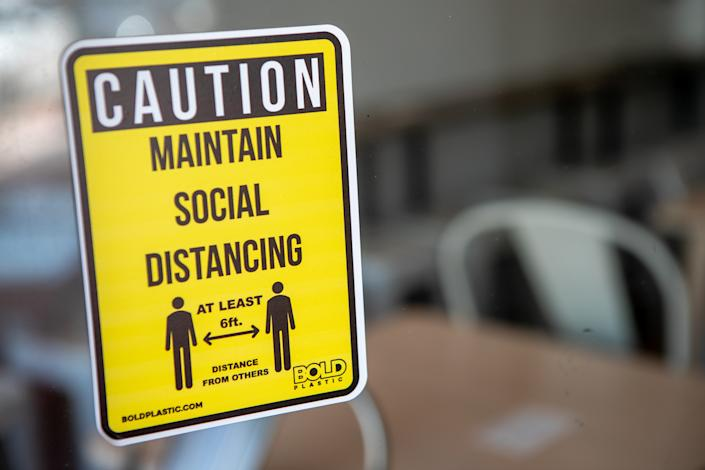 A social distancing sign is displayed in the window of a business in Miami, Florida, U.S., on Wednesday, July 8, 2020. (Jayme Gershen/Bloomberg via Getty Images)