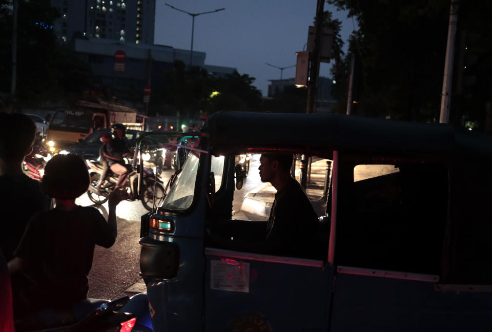 A three-wheeled motorized taxi driver is silhouetted by the lights from incoming traffic as he is stuck in traffic during a power outage in Jakarta, Indonesia, Sunday, Aug. 4, 2019. Indonesia's sprawling capital and other parts of Java island have been hit by a massive power outage affecting millions of people. (AP Photo/Dita Alangkara)