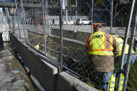 Workers install concertina wire between fenced barriers outside the Hennepin County Government Center, Wednesday, Feb. 23, 2021 in Minneapolis, as part of security in preparation for the trial of former Minneapolis police officer Derek Chauvin. The trial is slated begin with jury selection on March 8. Chauvin is charged with murder the death of George Floyd during an arrest last May in Minneapolis. (AP Photo/Jim Mone)