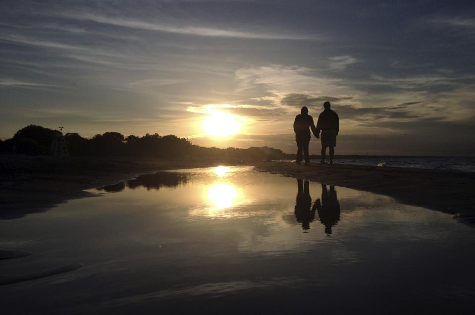 REFILE - ADDING DATE A couple walks along Gillson Beach holding hands as the sun sets in Wilmette, Illinois, June 14, 2014. REUTERS/Jim Young (UNITED STATES - Tags: ENVIRONMENT SOCIETY)
