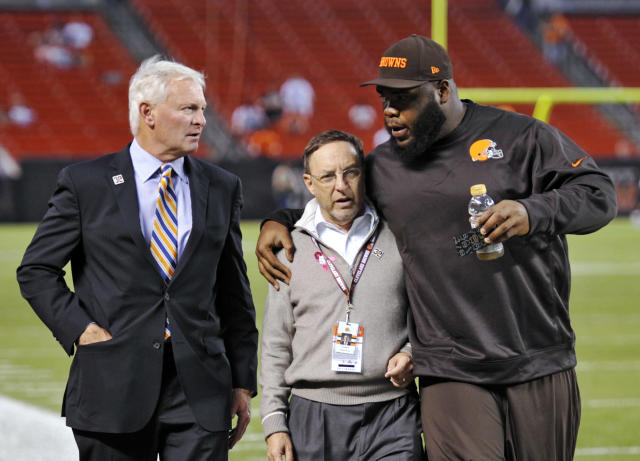 Cleveland Browns nose tackle Phillip Taylor, right, hugs team CEO Joe Banner as they walk with team owner Jimmy Haslam, left, before an NFL football game against the Buffalo Bills on Thursday, Oct. 3, 2013, in Cleveland. (AP Photo/David Richard)