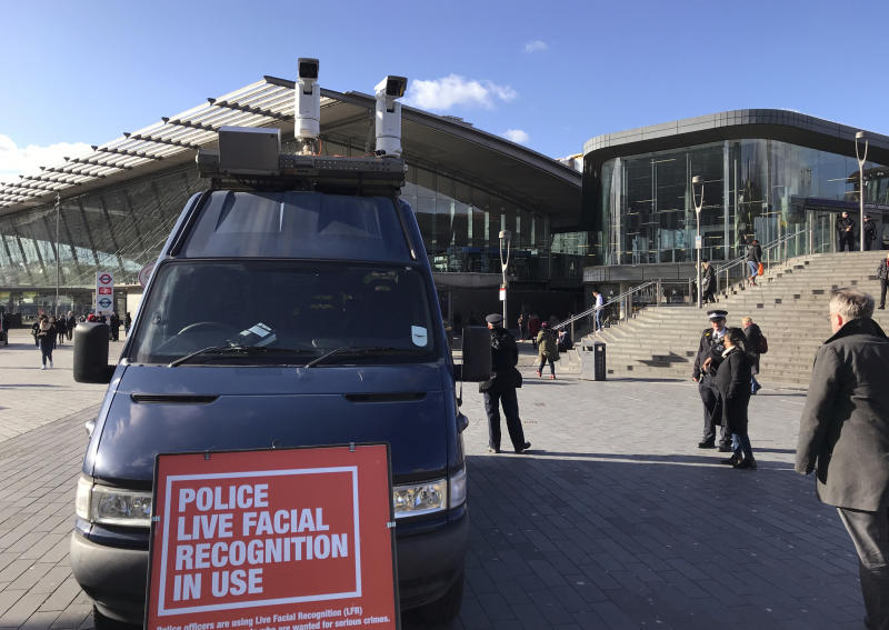 "A mobile police facial recognition facility outside a shopping centre in London Tuesday Feb. 11, 2020, ""We don't accept this. This isn't what you do in a democracy,"" said Silkie Carlo, director of privacy campaign group Big Brother Watch, who are demonstrating against the surveillance.  London police started using facial recognition surveillance cameras mounted on a blue police van on Tuesday to automatically scan for wanted people, as authorities adopt the controversial technology that has raised concerns about increased surveillance and erosion of privacy. (AP Photo/Kelvin Chan)"