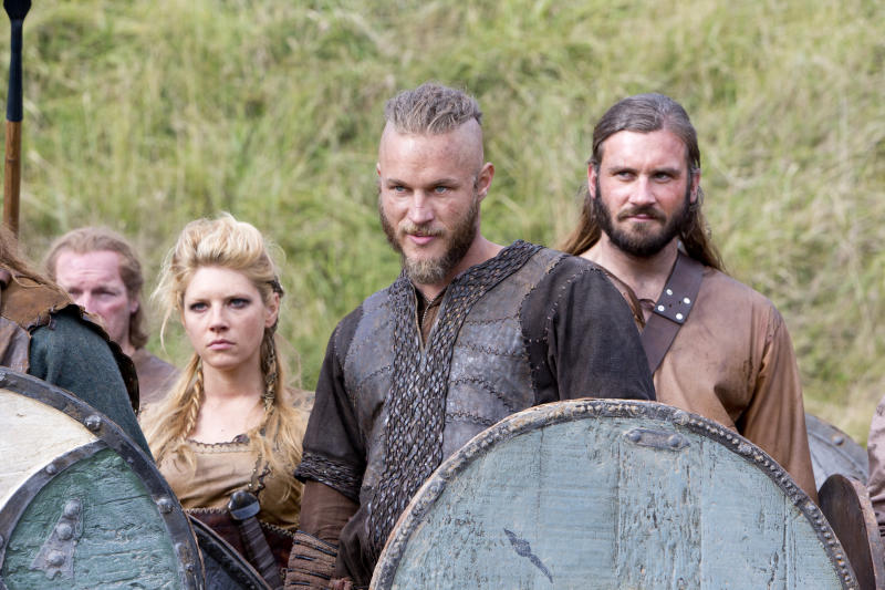 """This image released by History shows Katheryn Winnick, as Lagertha, left, Travis Fimmel, as Ragnar, center, and Clive Standen as Rollo in a scene from """"Vikings,"""" premiering Sunday, March 3 on History. (AP Photo/History, Jonathan Hession)"""