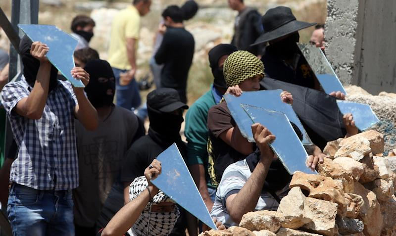 Palestinian protesters carry parts of a broken mirror during clashes with Israeli forces in the West Bank village of Kfar Qaddum on May 15, 2015 (AFP Photo/Jaafar Ashtiyeh )