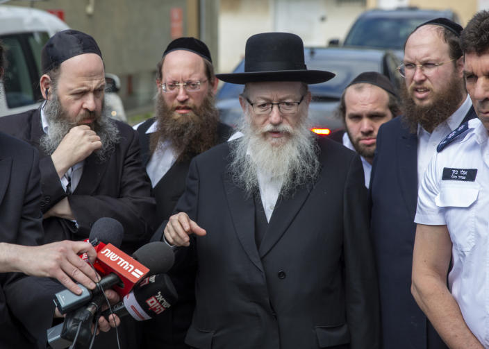 In this Monday, March 2, 2020 photo, Israel's Health Minister Yaakov Litzman delivers a statement as he visits a makeshift tent for quarantined coronavirus voters in Tel Aviv, Israel. Litzman, who has had frequent contact with Prime Minister Benjamin Netanyahu and other top officials, has the new coronavirus, the Health Ministry announced Thursday. (AP Photo/Ariel Schalit)