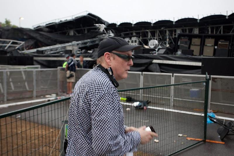 Rick Nielsen, the lead guitarist for the rock band Cheap Trick, walks past the main stage at Ottawa Bluesfest after it collapsed in Ottawa, Ontario on Sunday July 17, 2011. The main stage at Ottawa Bluesfest collapsed during a severe thunderstorm that sent thousands of people running for cover. Bluesfest said there were no serious injuries.  (AP Photo/The Canadian Press, Leon Switzer)
