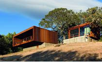 """Comprising two prefab corrugated steel boxes on concrete plinths, Alchemy Architects' Sonoma weeHouse takes full advantage of its hillside location. The main home includes a central """"bed box"""" separating the living room and bathroom, and the other structure serves as a guest house."""