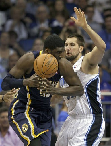 Indiana Pacers' Roy Hibbert, left, loses his grip on the ball as he is guarded by Orlando Magic's Ryan Anderson during the first half of Game 4 of an NBA first-round playoff basketball series, Saturday, May 5, 2012, in Orlando, Fla. (AP Photo/John Raoux)